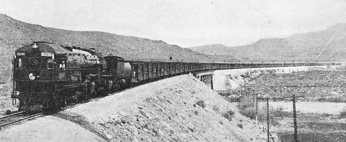 "A SEVENTY-WAGONS FREIGHT TRAIN on the Southern Pacific Railroad being hauled by one of the large oil-fired 4-8-0+0-8-4 articulated engines of the ""4100"" class"