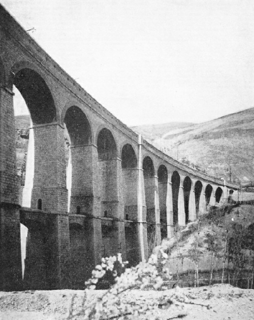 ON THE ROME-SULMONA ROUTE. The line has been electrified, and the standards supporting the overhead conductors can be seen on the viaduct