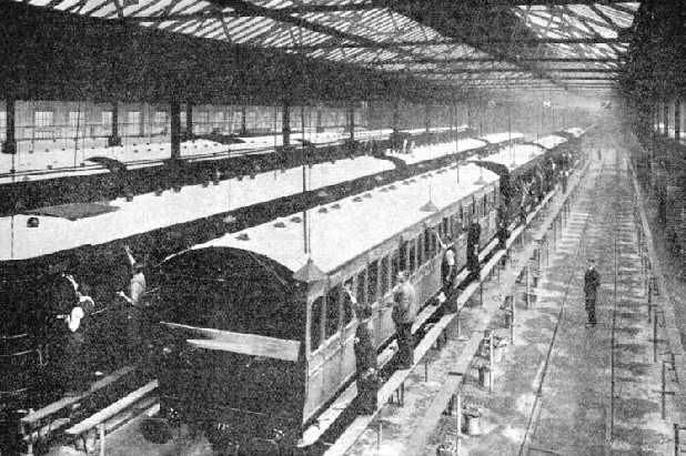 Rows of coaches owned by the Southern Railway receiving a fresh coat of paint in the Company's works at Lancing, Sussex
