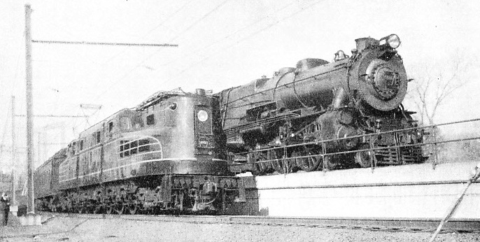 "One of the latest streamlined electric locomotives of the Pennsylvania Railroad alongside a standard ""Pacific"""