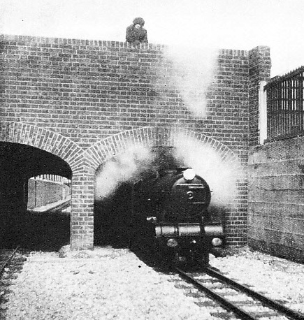 A MINIATURE BRIDGE carries the road over the double track of the Romney, Hythe and Dymchurch Railway