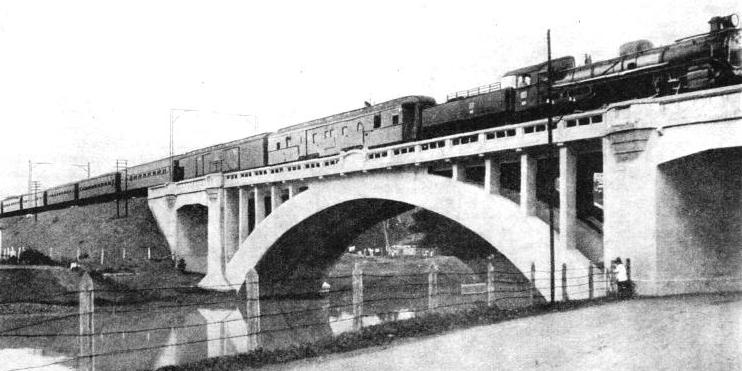 The Batavia-Djokja express crossing a concrete viaduct near the Weltevreden Station, Java